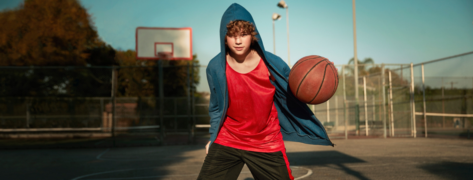 young boy in blue hoodie dribbles basketball by himself on court