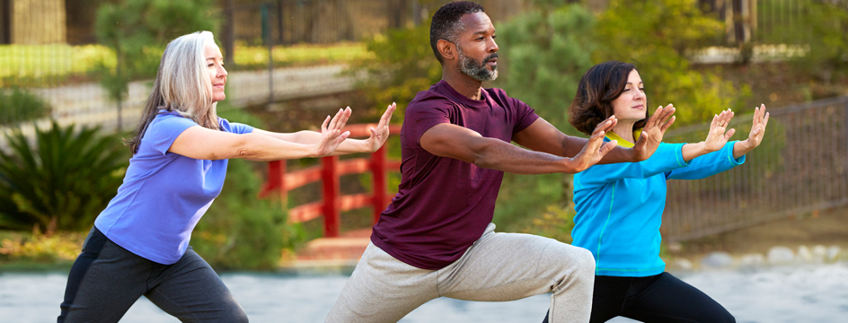 A man and two women doing yoga in the park at sunset