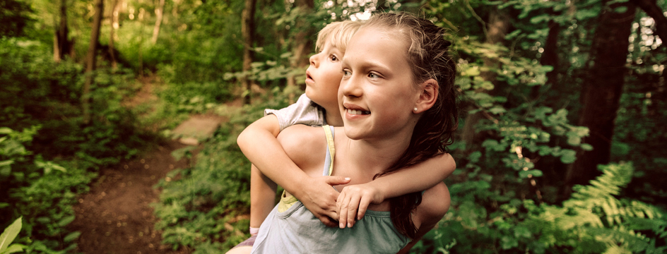 Young girl carries her sister on her back for a walk through the woods