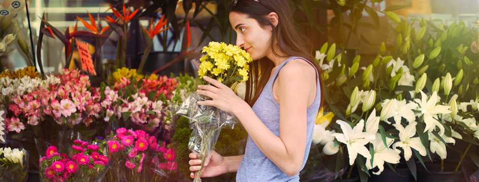 Woman stops to smell flowers outside of flower store